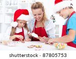Family decorating christmas cookies together in the kitchen - stock photo