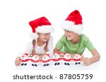 Mischievous christmas kids waiting for santa holding paper decoration - stock photo