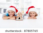 Happy kids with their gingerbread house in the kitchen at christmas time - stock photo