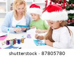 Family making seasonal greeting cards together at christmas time - stock photo