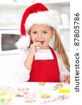 Little girl decorating christmas cookies tasting the icing - stock photo