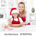 Woman and little girl stretching the christmas gingerbread cookies dough - stock photo