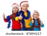 Three children in Santa hats showing thumb up sign, isolated on white - stock photo
