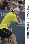 NEW YORK - AUGUST 31: John Isner of USA returns ball during 1st round match against Marcos Baghdatis of Cyprus at USTA Billie Jean King National Tennis Center on August 31, 2011 in New York City. - stock photo