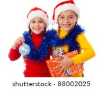 Two smiling girls in Santa hat with gift box and Christmas decoration, isolated on white - stock photo