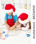 Kids making christmas cookies cutting the dough - stock photo
