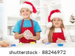 Kids making christmas cookies wearing santa hats and aprons - stock photo