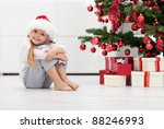 I have lots of presents - smiling little girl in front of the christmas tree - stock photo