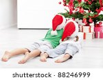 Kids admiring the christmas tree laying on the floor - stock photo