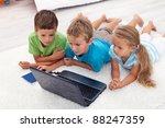 Three kids looking at laptop computer screen laying on the floor - stock photo