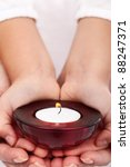 Child and adult hands holding candle - passing on traditions concept - stock photo
