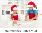 Happy kids with santa hats making christmas cookies - stock photo