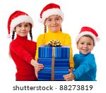 Three smiling kids in Santa hats with gift box, isolated on white - stock photo