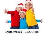 Three smiling children in Santa hats showing thumb up sign, isolated on white - stock photo