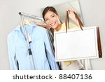 Shopper woman showing shopping bag sign with copy space for text. Woman standing by clothes rack in clothing store. Happy smiling multiracial Caucasian / Asian female model. - stock photo