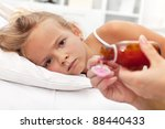 Sick little girl with flu awaiting medication- focus on the eyes - stock photo