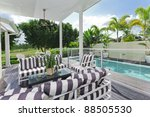 Stylish wooden outdoor deck overlooking a swimming pool and golf course - stock photo