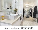 Stylish master bathroom with twin sinks and spacious walk in robe - stock photo