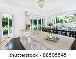 Stylish open kitchen with large dining table overlooking a golf coarse and swimming pool - stock photo