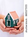Protect your home - hands holding small house - insurance concept - stock photo