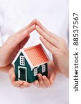 Protect your home - small house shielded with hands - stock photo