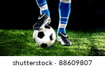 soccer ball with his feet on the football field - stock photo