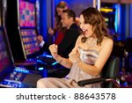 Friends in Casino on a slot machine; all obviously are winning - stock photo