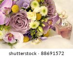 Wedding bouquet, rings and perfume bottle, soft focus. - stock photo