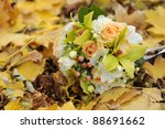 Wedding bouquet on bright autumn leaves in park. Soft focus. - stock photo