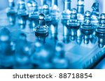 glass chess pawn in front with shallow depth of field in blue light - stock photo