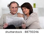 Small photo of Couple reading the newspaper together