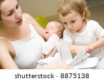 mother of two babies  reading a ... | Shutterstock . vector #8875138