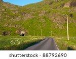 Uttakleivveien, single lane road on Lofoten Islands leading into narrow tunnel - stock photo