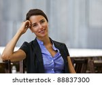 Pretty and young woman sitting outdoor - stock photo