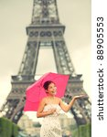 Eiffel Tower Paris woman. Cute beautiful young woman in dress smiling happy standing with red umbrella in front of Eiffel tower, Paris, France. Asian / Caucasian female model. - stock photo