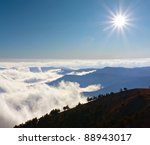 Mountain's scene with sun over clouds on mountains range - stock photo