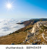 Mountain landscape with sunshine over clouds - stock photo