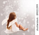 Little angel thinking in divine light while sitting - stock photo
