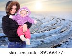 Young mother with cute baby dressed in a fur in winter cold weather. Seasonal fashion shot. - stock photo
