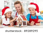Our christmas gingerbread cookie house - family in the kitchen at holidays time - stock photo