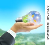 Businessman holding light bulb on blue sky and green mountain. - stock photo