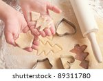 little girl cutting christmas gingerbread cookies, hands only - stock photo