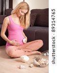 Young pregnant blonde woman sitting on the floor with shells - stock photo