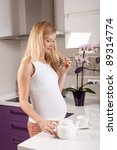 Young pregnant blonde woman preparing tea in kitchen - stock photo