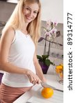 Young pregnant blonde woman cutting orange in kitchen - stock photo