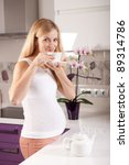 Young pregnant blonde woman drinking tea in kitchen - stock photo