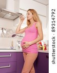 Young pregnant blonde woman drinking water in kitchen - stock photo