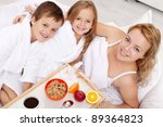 Breakfast in bed for mom-kids pampering their mother - stock photo