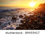 Small photo of Sea coast with wet rocks and with red algae (Rhodophyta) at sunset light