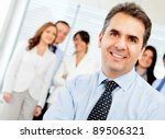 Successful business leader with a group on the background - stock photo